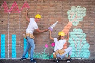 Ferry Spigt en Wendy Briggeman krijten op een stenen muur een bos vol bomen die omgezaagd worden in de kindervoorstelling Baas in het bos