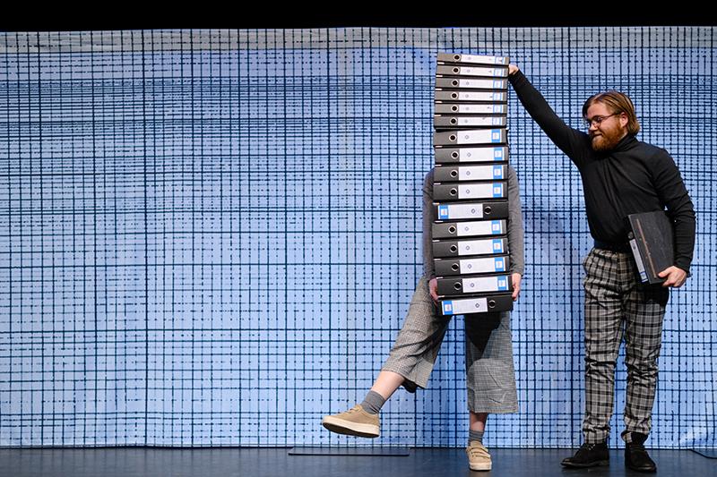 Tessa is niet meer zichtbaar achter de stapel mappen in de mime voorstelling voor kinderen